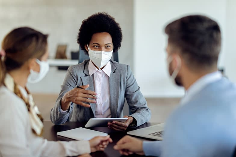 Happy African American Financial Advisor Consulting Her Clients While Wearing Protective Face Mask On A Meeting.