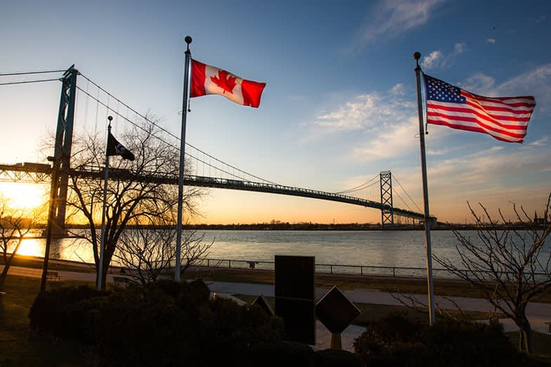 The Ambassador Bridge links Detroit, Michigan, USA with Windsor, Ontario, Canada.  It is one of the busiest trade routes in North America.  This photo depicts the bridge, as seen from Windsor.   The national flags of the USA and of Canada are notable in the foreground.