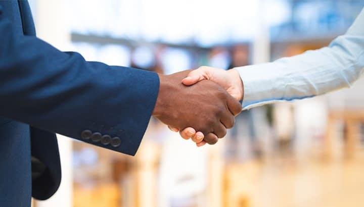 Mid section close-up of diverse Business people shaking hands with each other in corridor at office. International diverse corporate business partnership concept