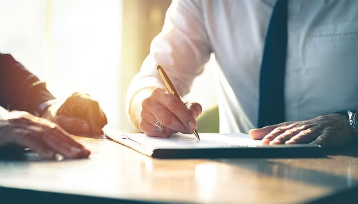 Closeup Businessman signing a contract investment professional document agreement on the table with pen.