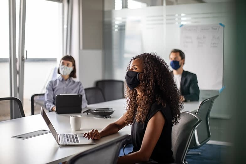 Team of business professionals wearing face mask sitting in office boardroom during a meeting. Business people having meeting during pandemic.