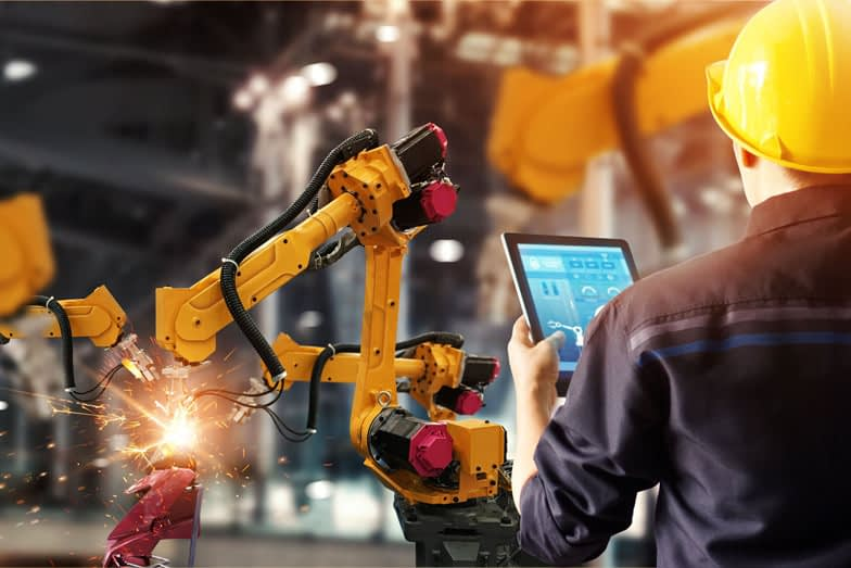 a worker holding a tablet computer watches robotic arms at work