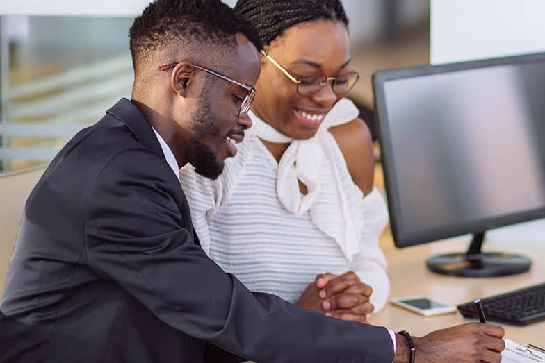 African Couple Getting Car Key From Dealer In Showroom And Signing Contract