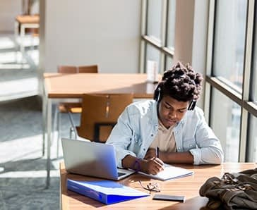 African American teenage boy writes something in a notebook while studying in the campus library. An open laptop is on the table. He is wearing wireless headphones.