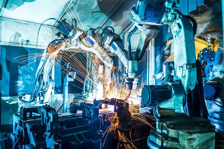 two robotic arms at work in a manufacturing facility