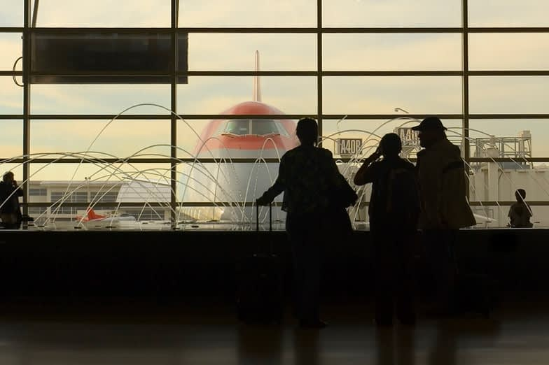 Silhouettes of travelers by a fountain looking at an airplane parked at a gate at Detroit Metro Airport.